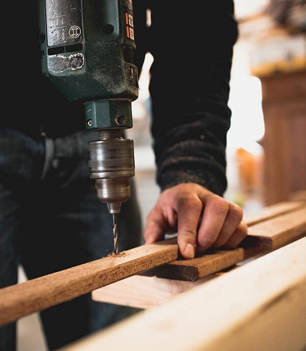 man-holding-wooden-stick-while-drilling